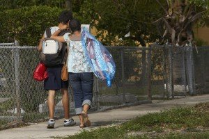 Rear view of a teenage boy and his sister walking on the walkway